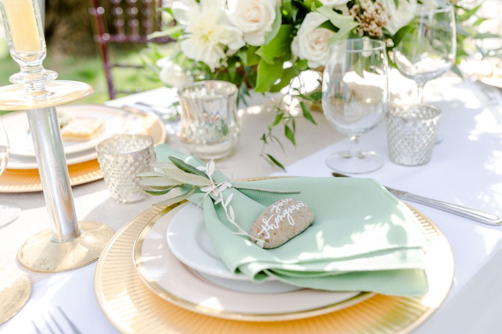 Elegant place setting with gold charger, white plates, pastel green cloth napkin, and scripted name setting on a rock